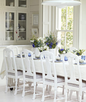 White dining room with high-backed chairs and glass and wood cabinets