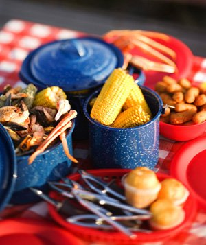 Picnic table with boiled crab, corn on the cobb, cornbread muffins on red checked tablecloth