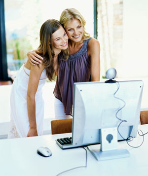 Mother and her daughter standing in front of a video conference camera on a computer monitor