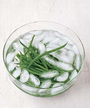 Green beans in a bowl of ice cubes