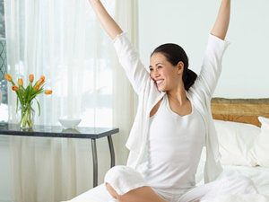 Happy woman stretching in bed