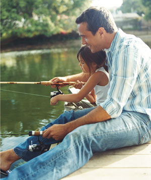 Dad fishing in a pond with his child