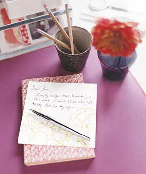 Pen and half-written letter next to a cup of pencils and a flower