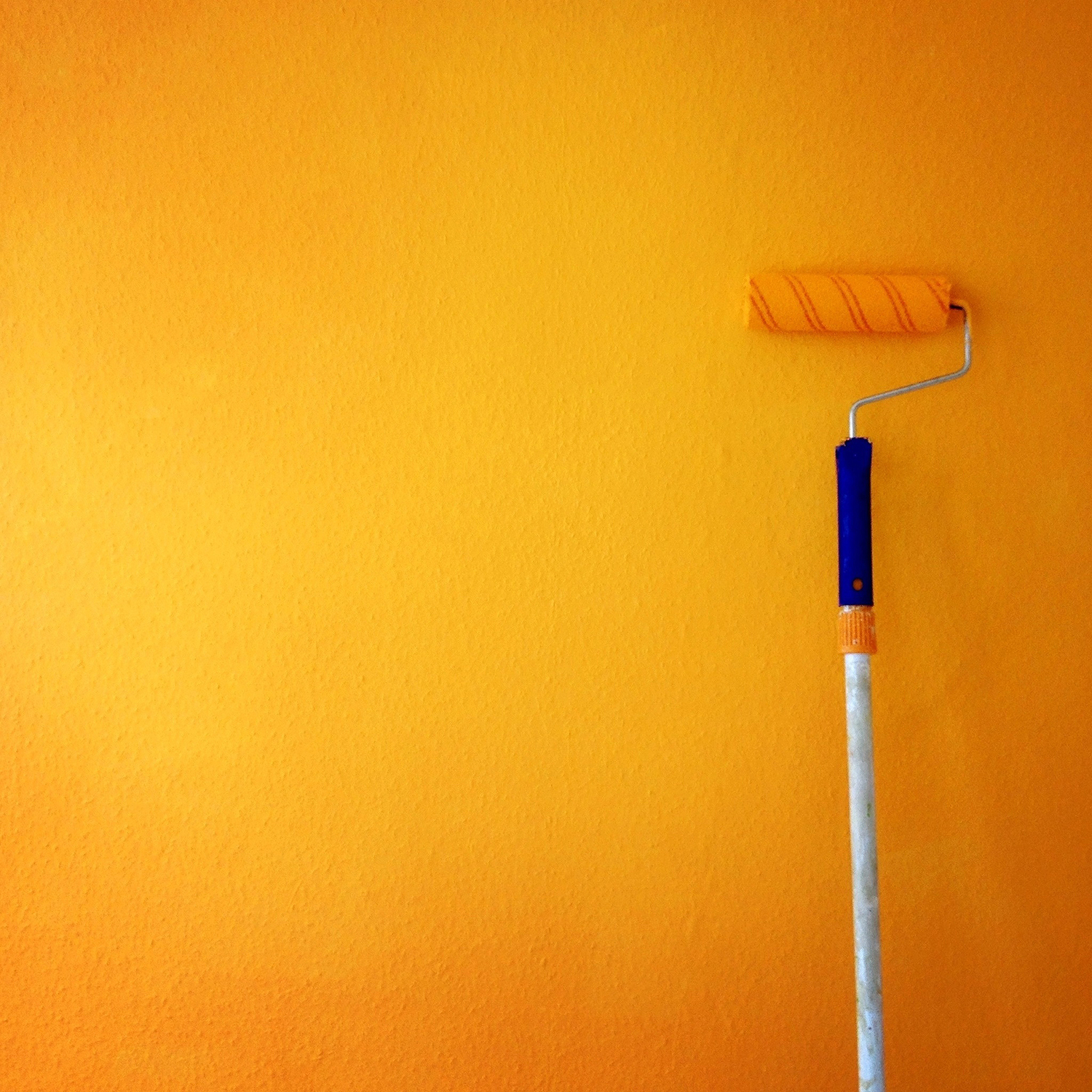 Paint roller leaning on yellow-orange accent wall