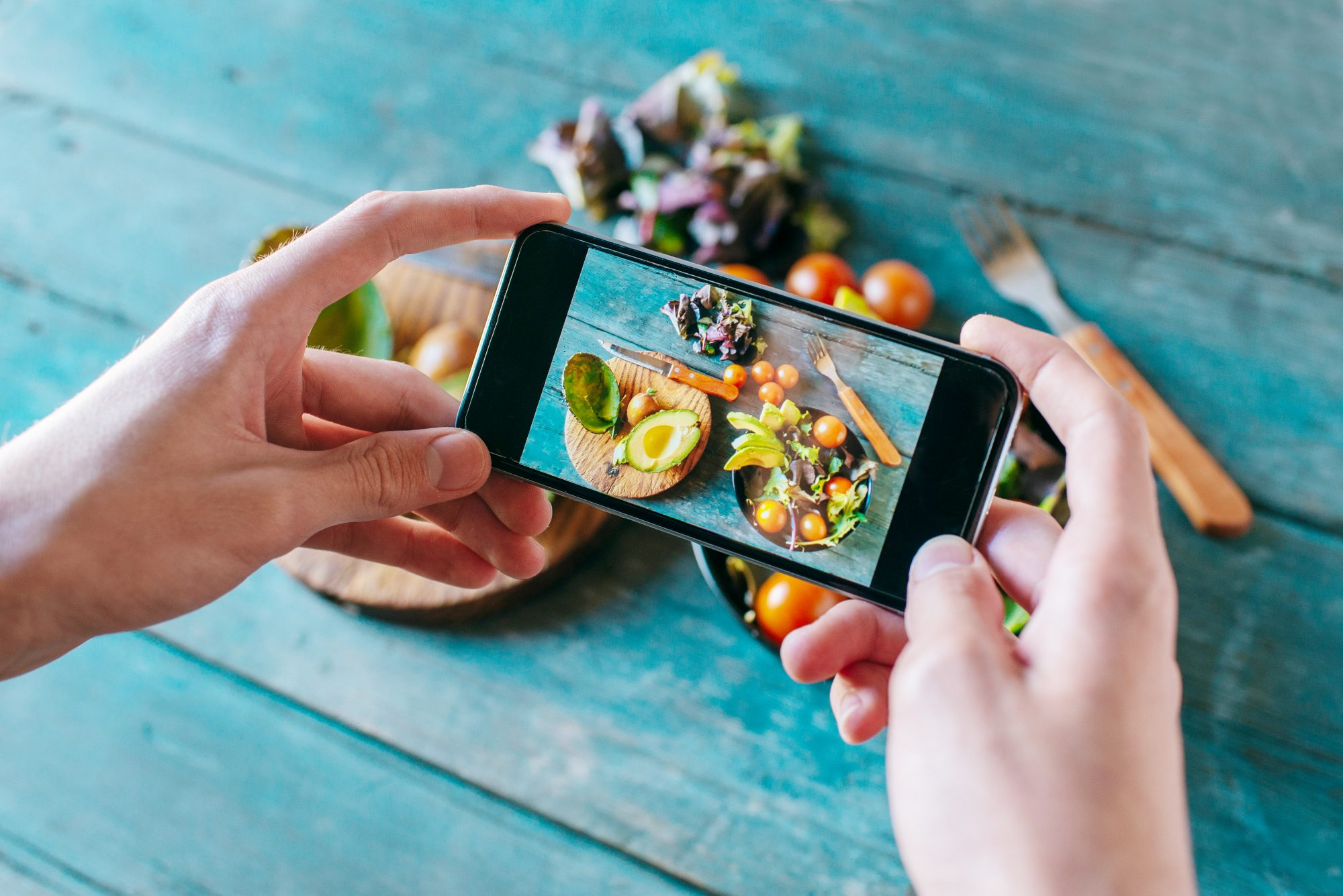 person taking a photo of their food with cell phone