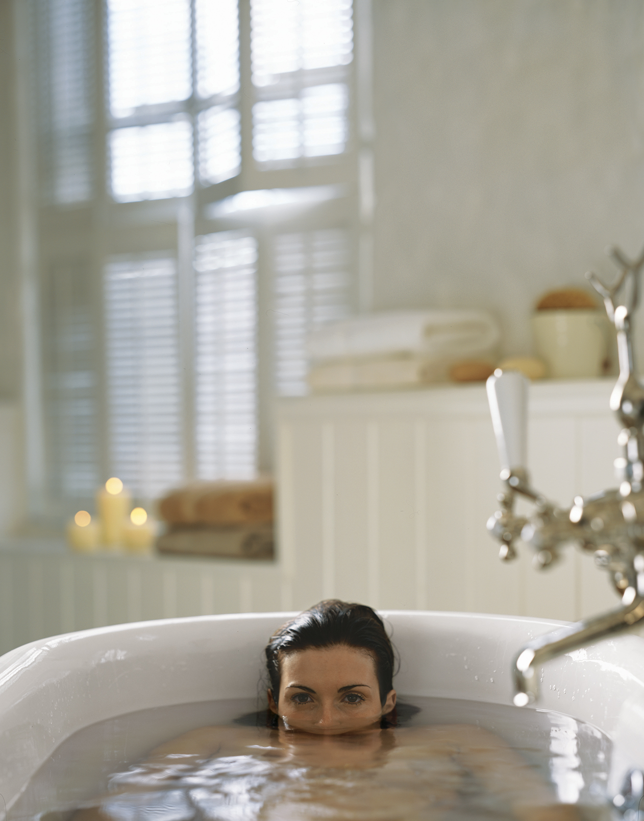 Woman in a bathtub with her head half submerged in water