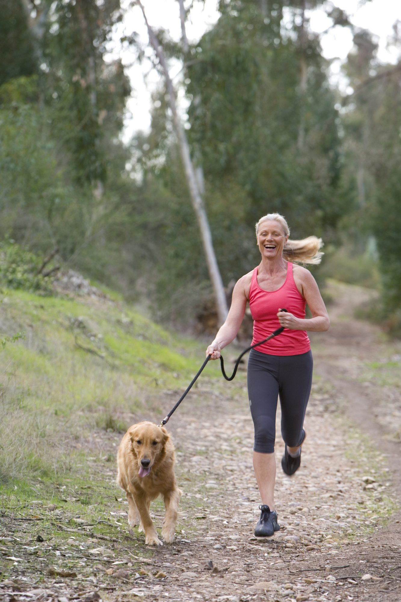 woman jogging with dog laughing outside