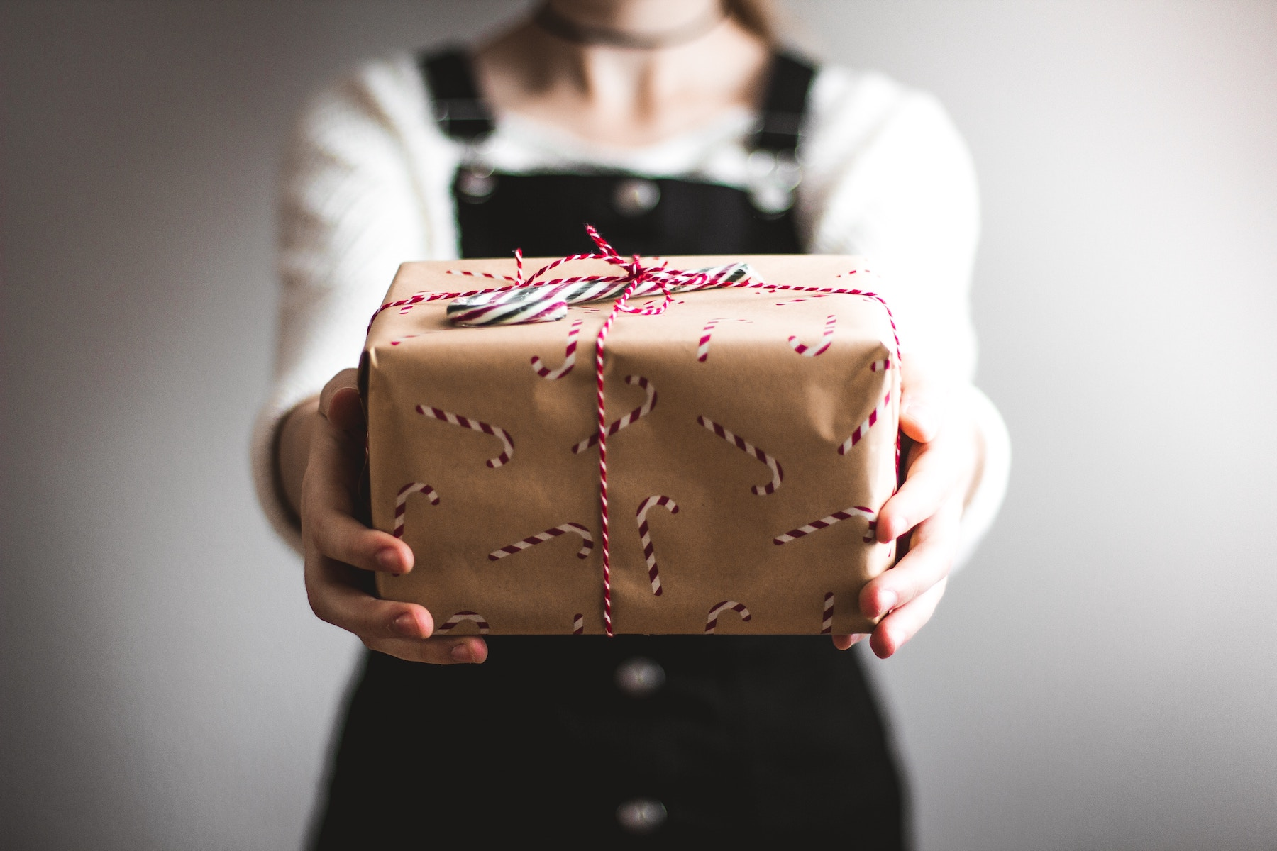 Woman presenting a wrapped gift with candy cane wrapping paper