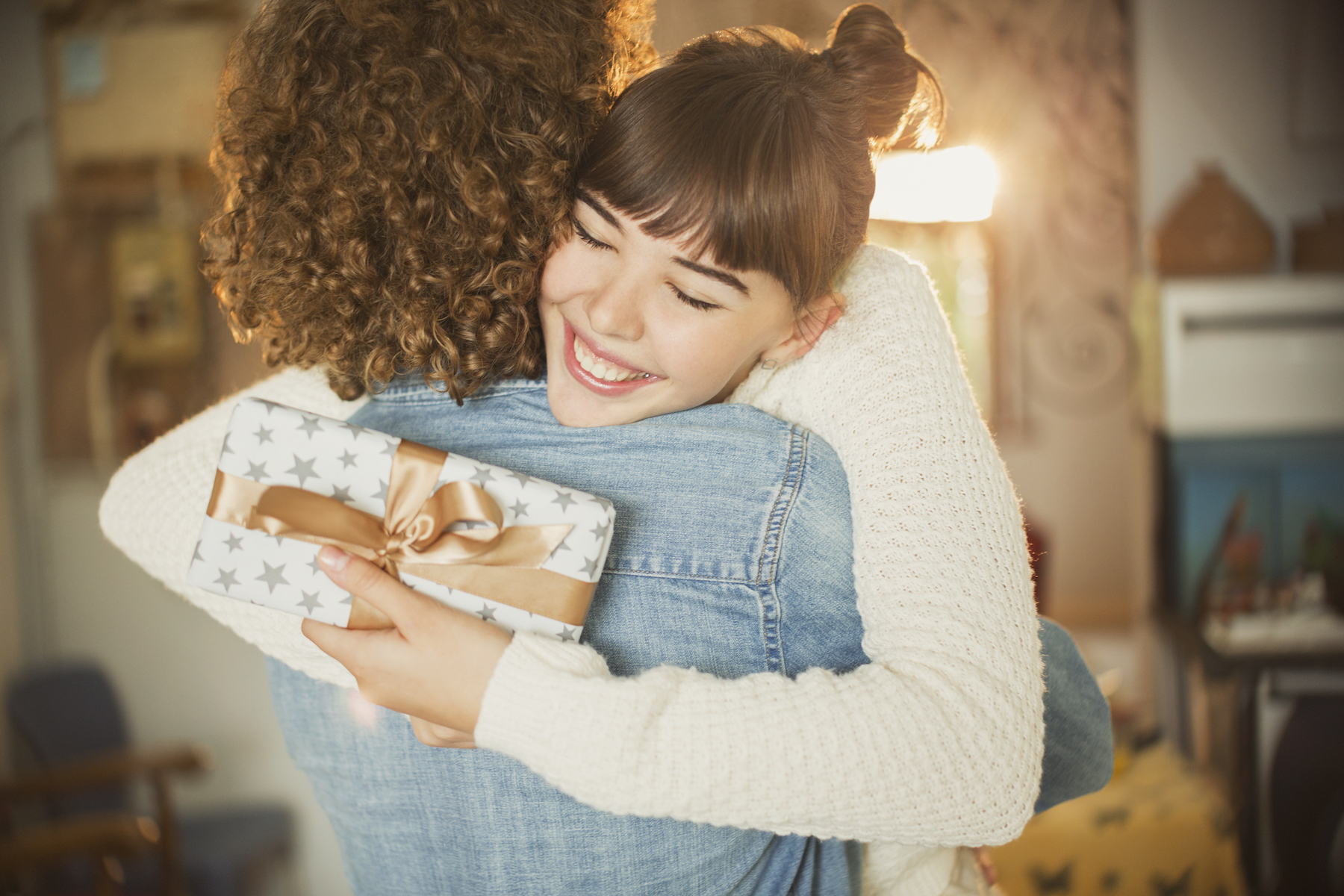Woman Holding Wrapped Present Hugging Boyfriend