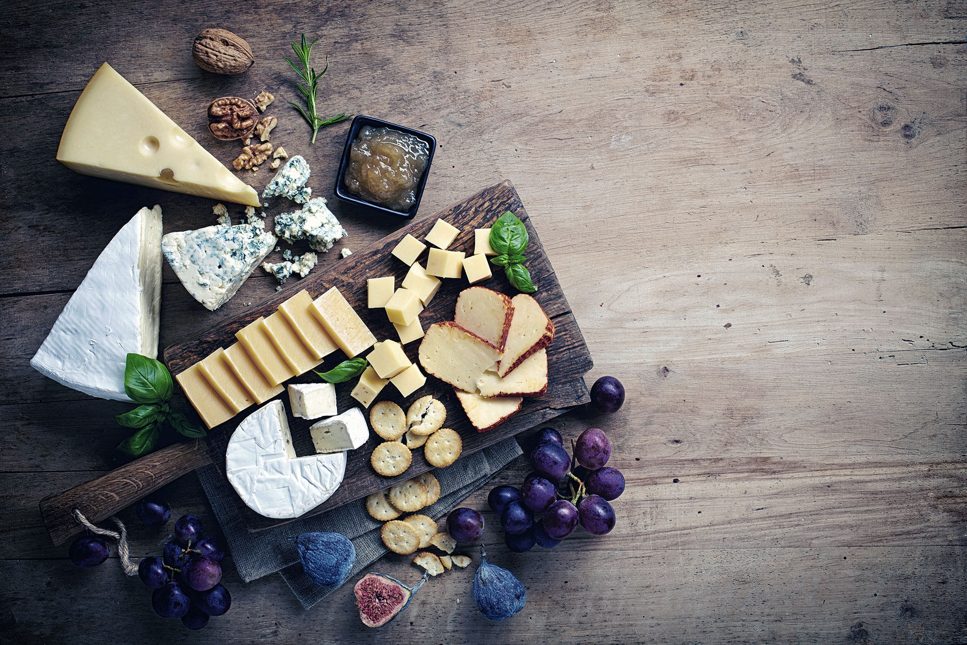 Cheese plate served with grapes, jam, figs, crackers and nuts