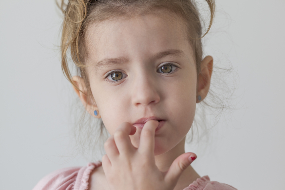 A Little Girl Biting Her Nails