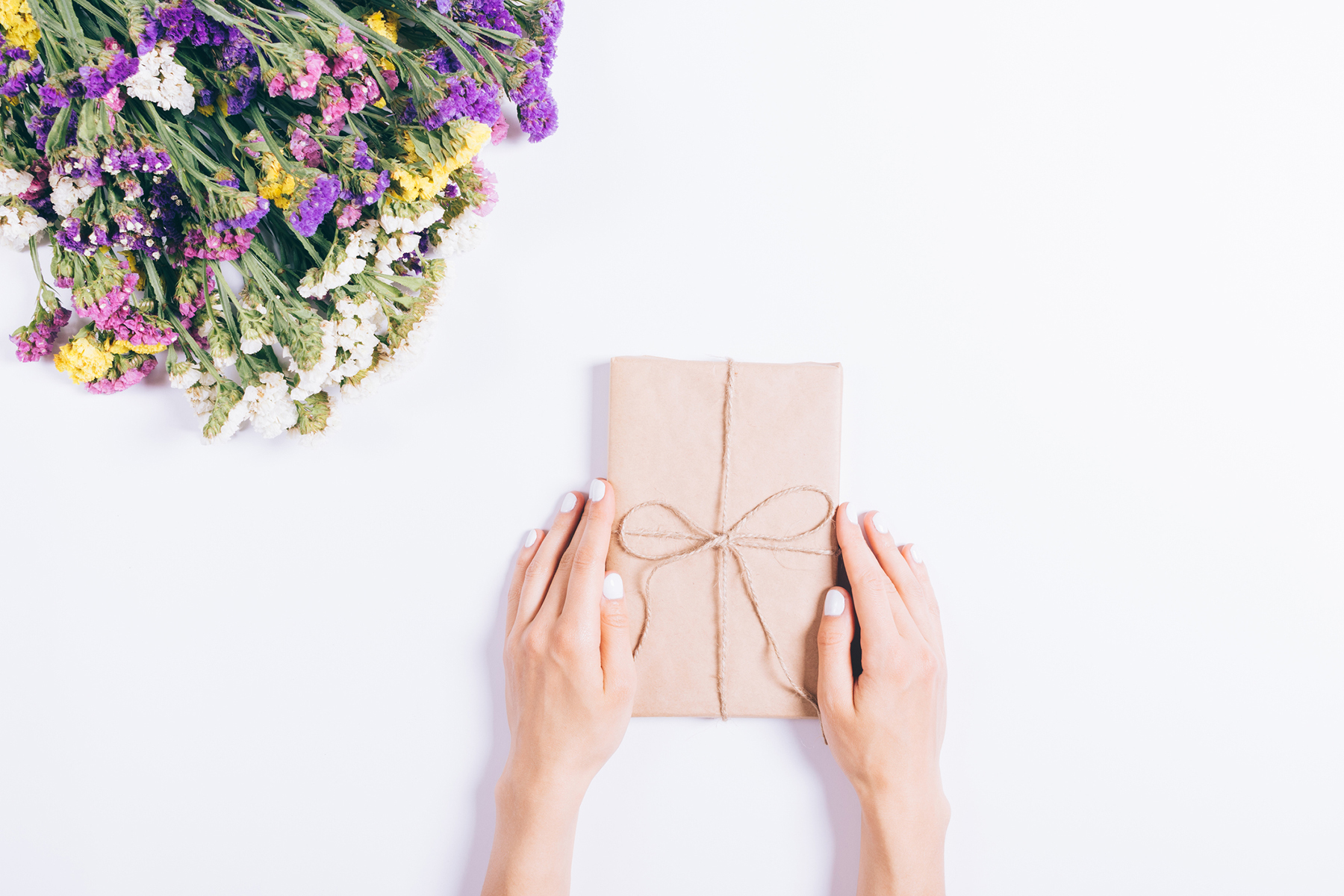 hands holding a wrapped book as a gift with a bouquet