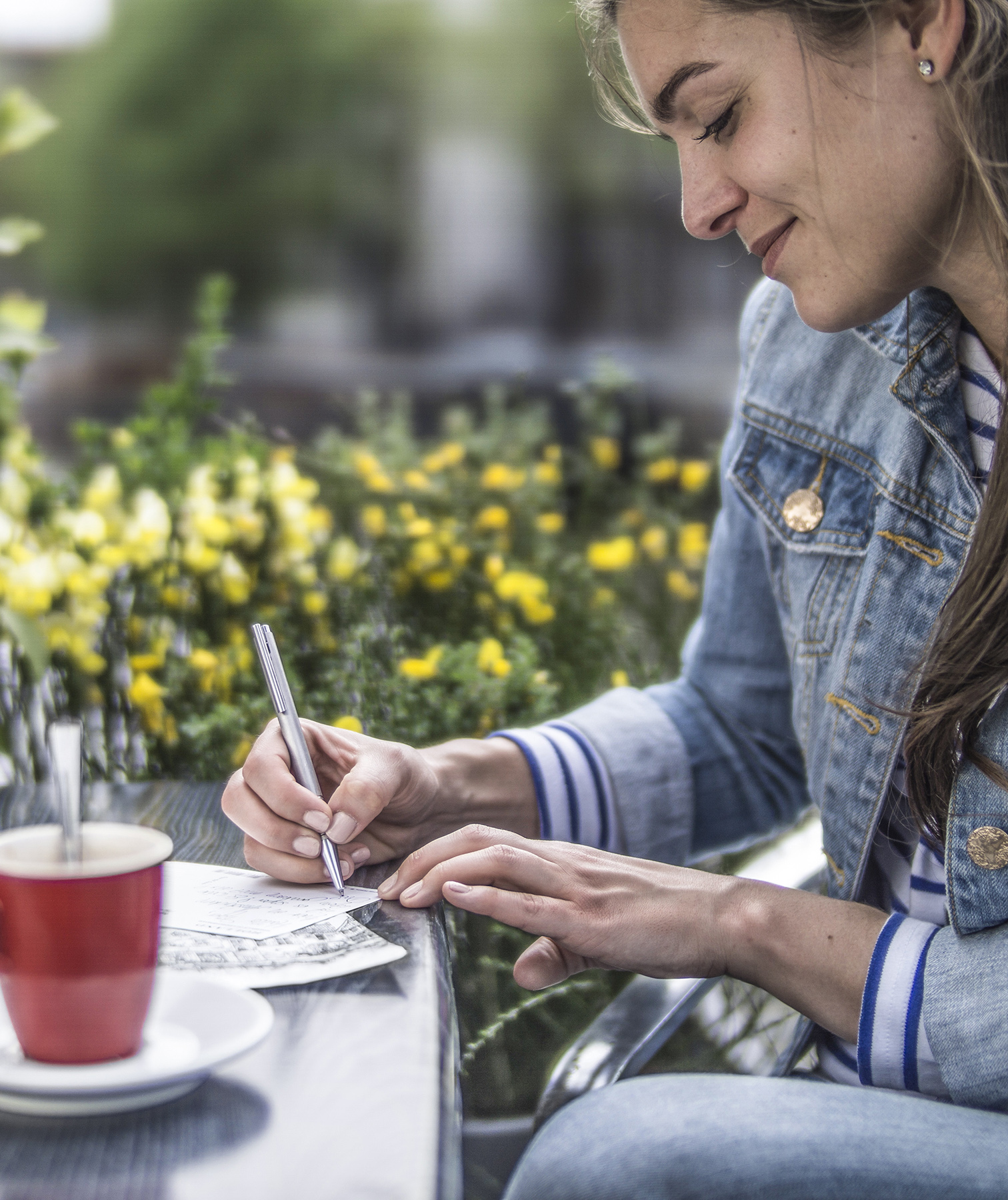 Woman writing letter at outdoor café