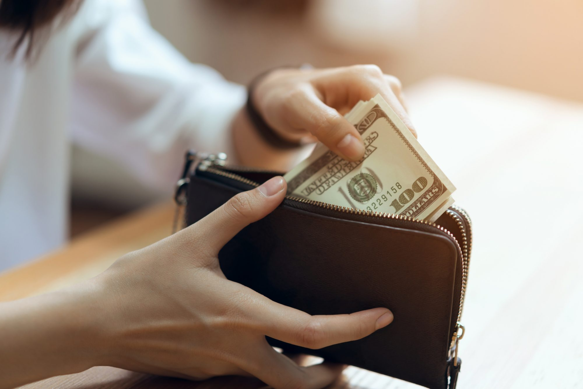 A woman puts money back into her wallet, after learning how to pay off debt.