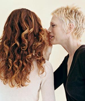 Woman whispering in another woman's ear