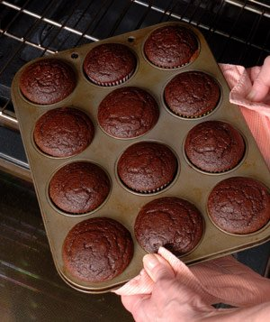 Hands taking baked cupcakes in cupcake tin off oven rack