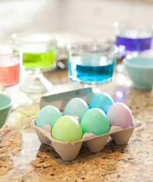 Colorful dyed Easter eggs in carton on counter