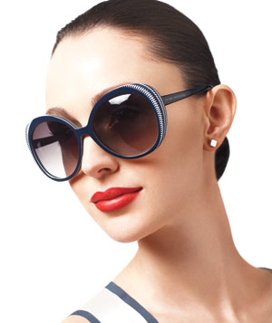 Model wearing dark rounded sunglasses and red lipstick