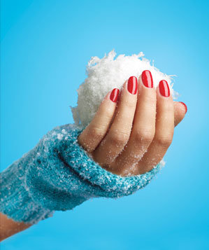 Hand with red nail polish holding snowball