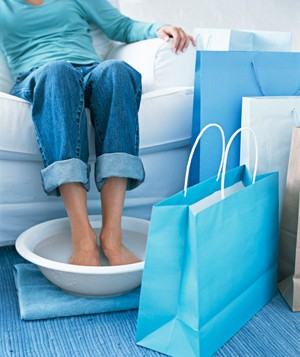 Woman soaking her feet next to shopping bags