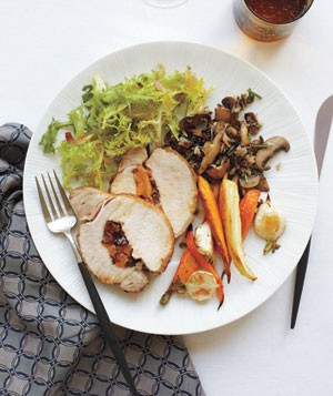 Holiday dinner featuring Stuffed Pork Loin With Roasted Root Vegetables