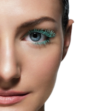 Half of model's face with peacock lashes