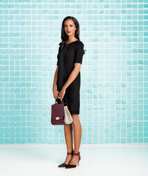 Model wearing black sleeved shift dress with burgundy bag and heels