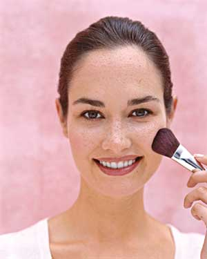 Woman applying blush with a brush