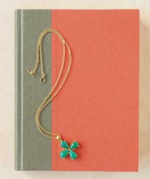 Four leaf clover chamr necklace on a book