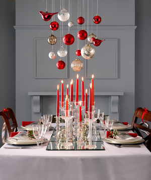 Holiday table with red ornaments and decorations