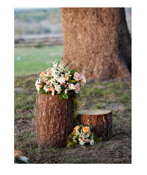 Wedding bouquets rest on a backyard tree stump