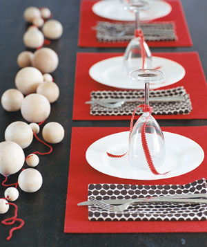 Table setting with red felt place mats and a wooden bead centerpiece
