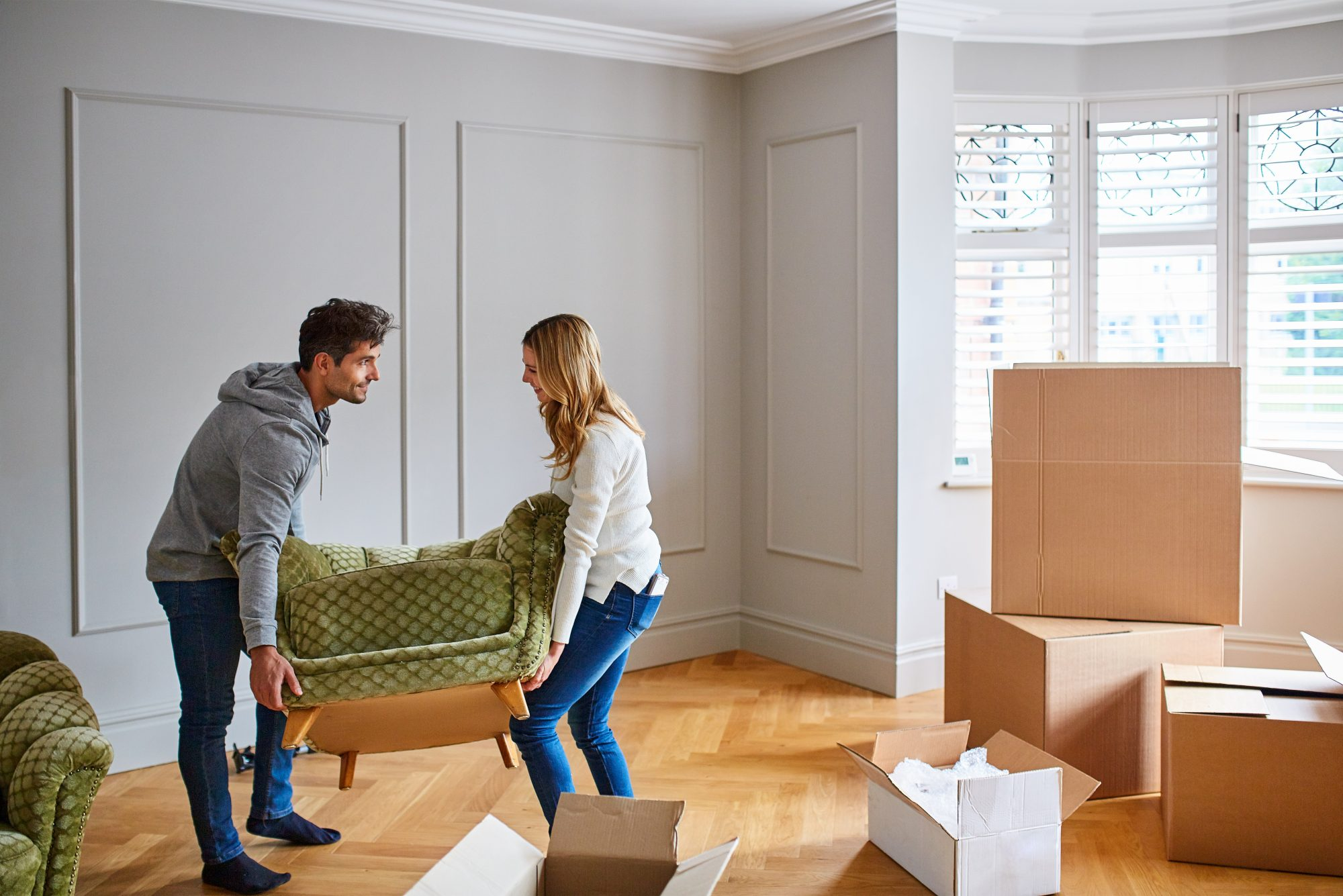 couple moving a chair surrounded by moving boxes