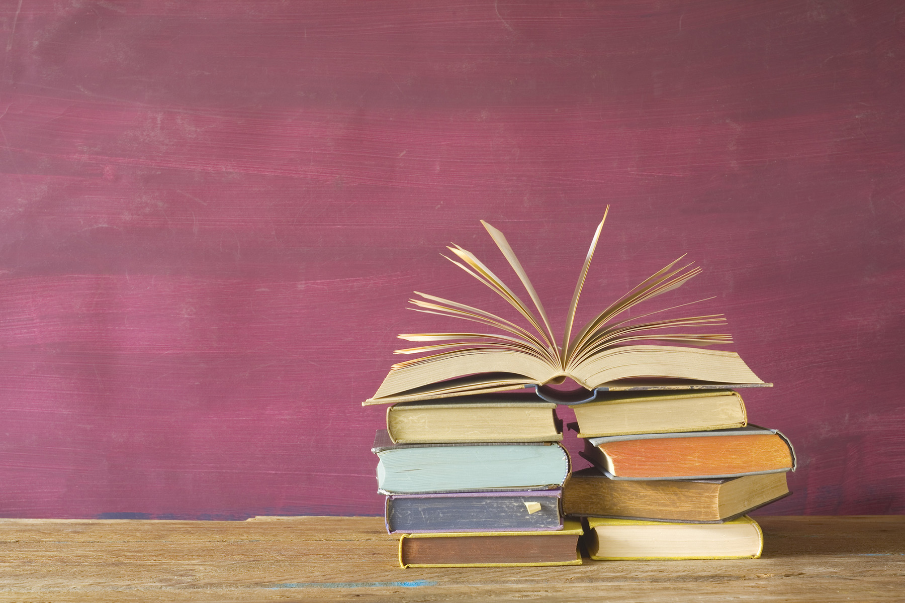 Stack of books against purple background