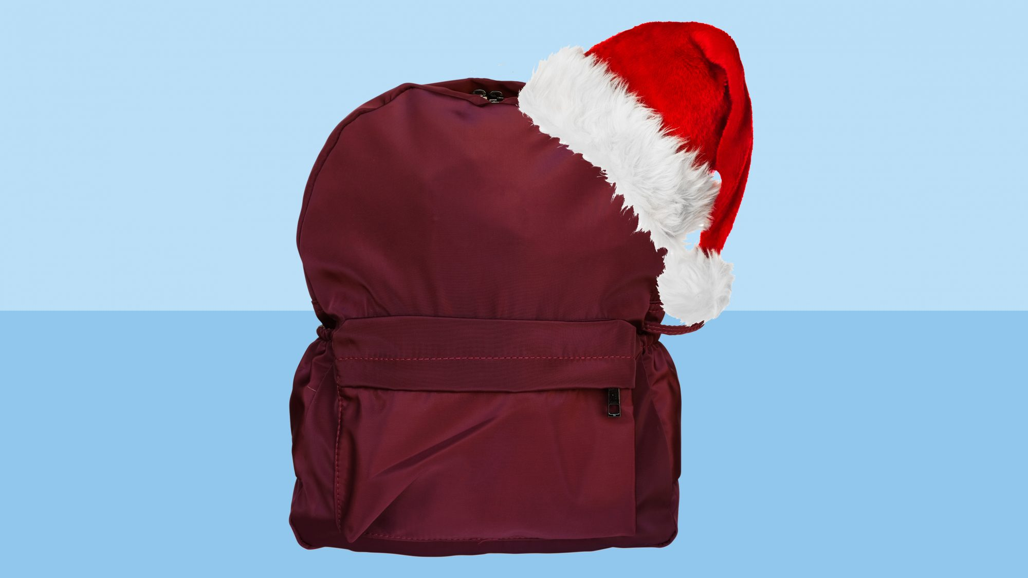 backpack with Santa hat on blue background