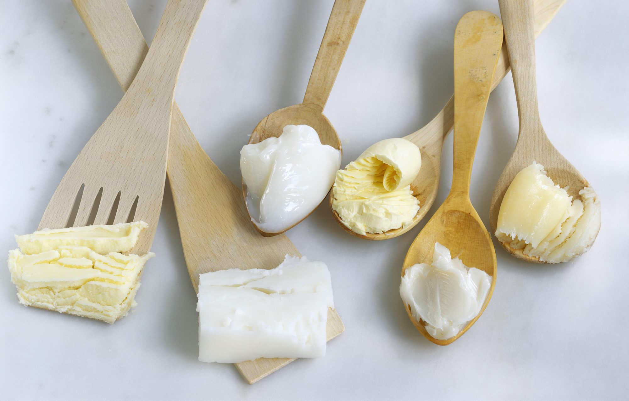 different types of butter on wooden spoons