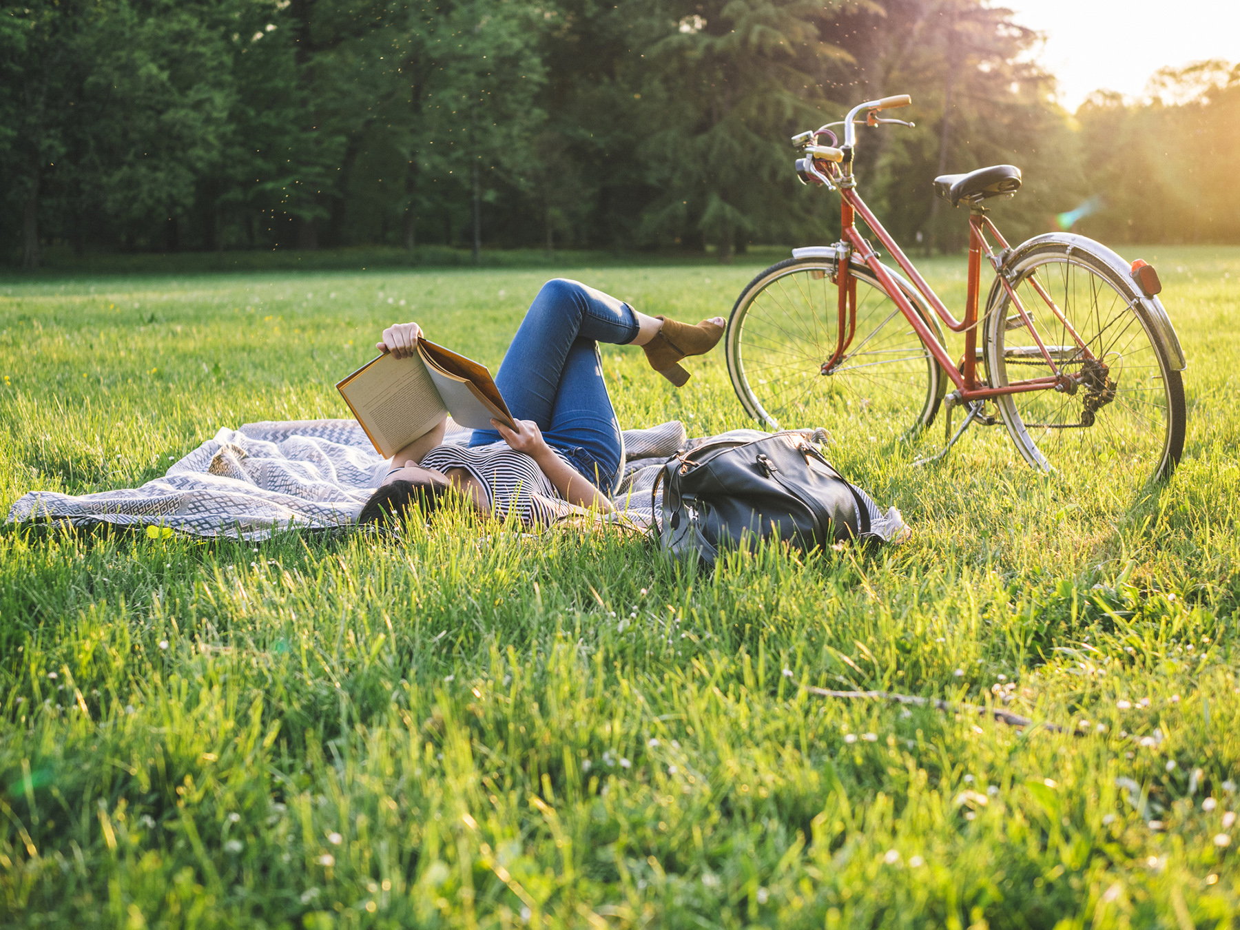 Woman reading book in grass with her bicycle