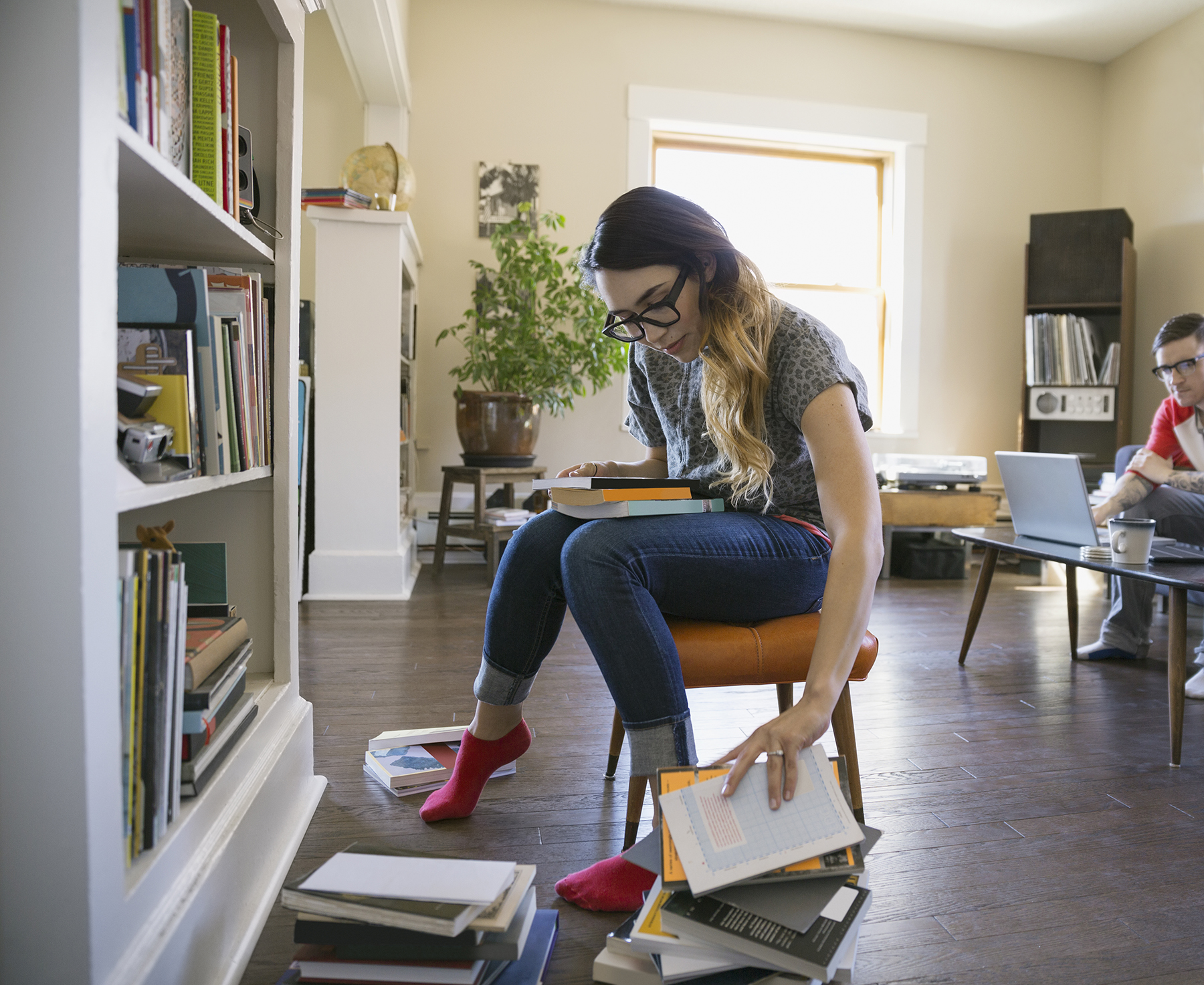 Woman sorting through books in living room