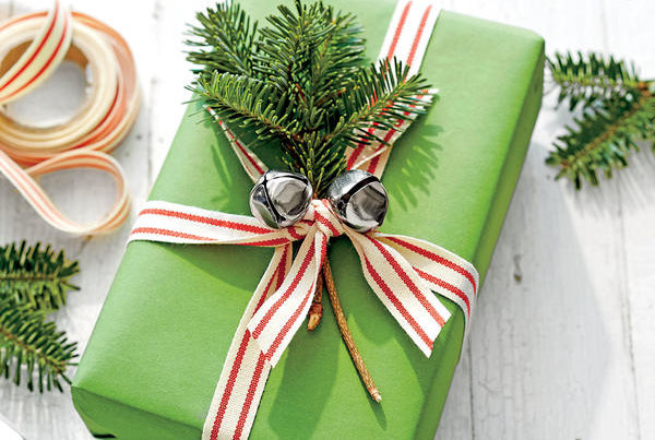 green wrapped christmas present with jingle bells ribbon and pine