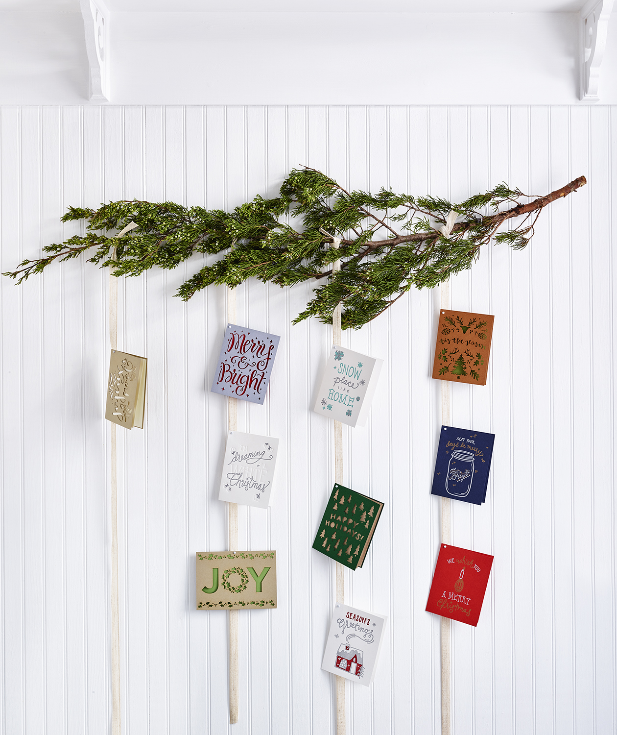 Holiday cards on wall with pine branch