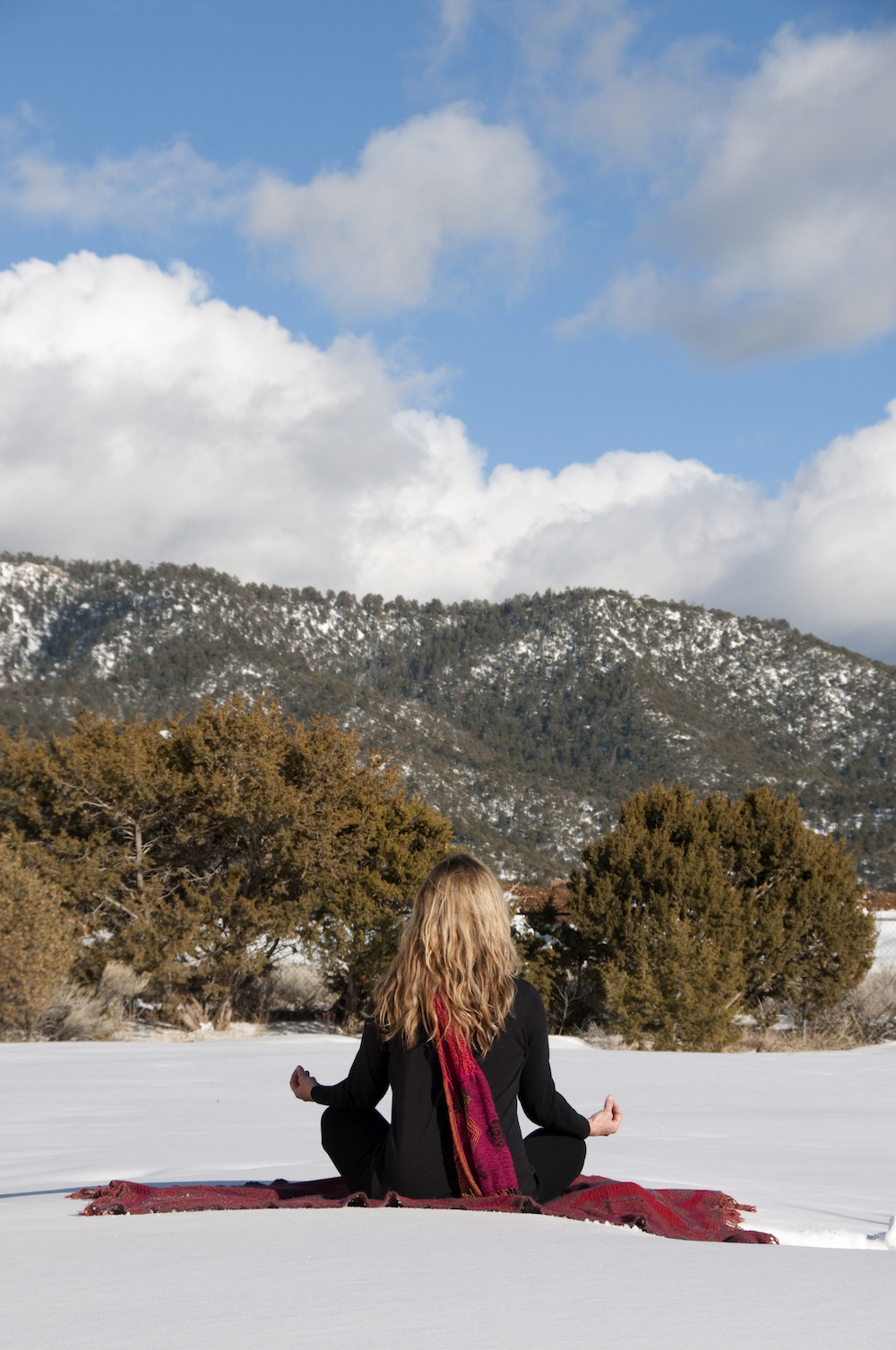 woman practicing yoga on mountain in snow