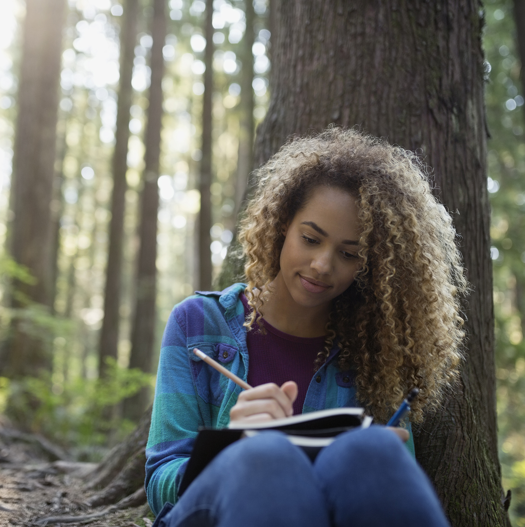 Woman writing in journal in woods