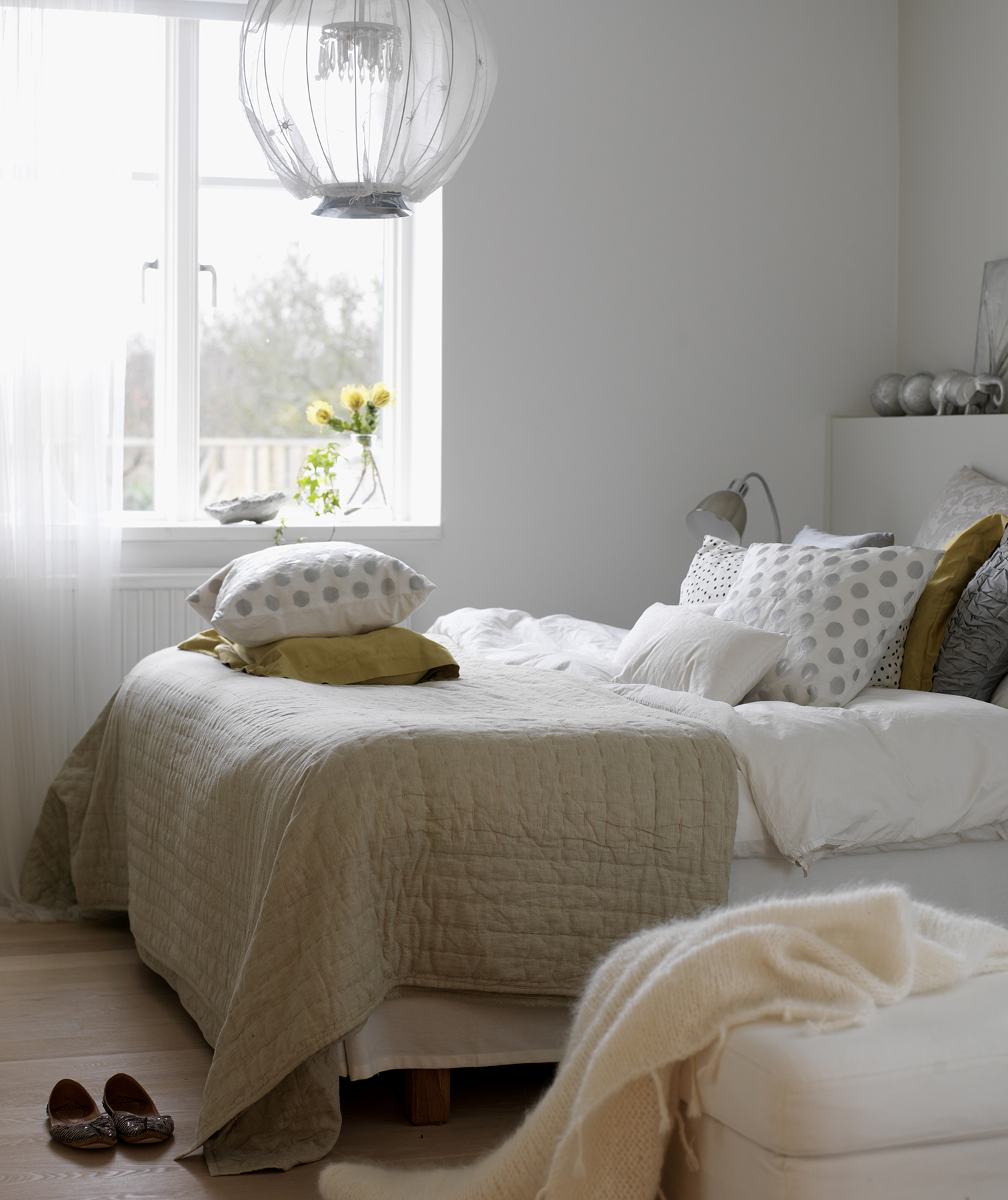 Light airy bedroom with pillows and throws