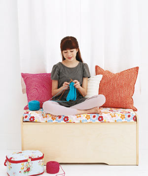 Toy box used as a window seat with colorful floral cushion