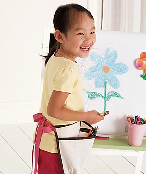 Little girl in front of an easel