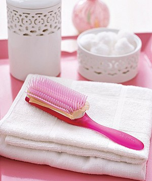 Pink hairbrush lying on a white towel