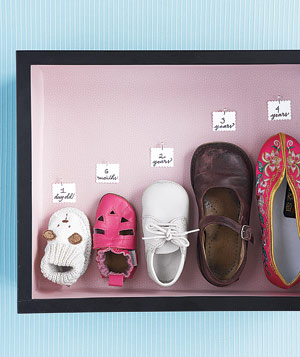 Shadow box of outgrown childrens shoes
