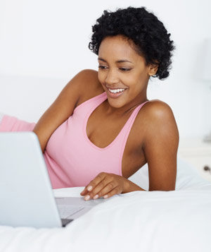 Smiling young woman working on laptop
