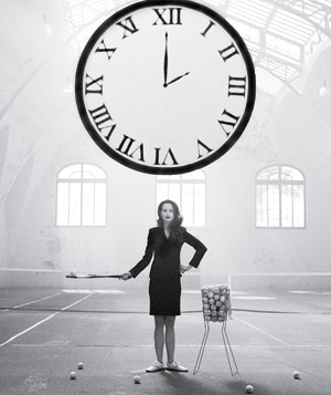 Black and white photograph of woman in business suit standing on tennis court with giant clock