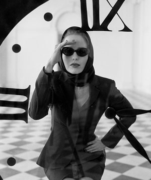 Black and white photograph of woman with sunglasses peering inside giant clock